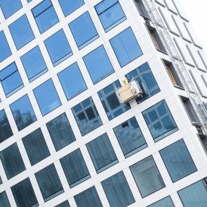 En fasad på Tripla. Fasaden är täckt av rektangulära fönster i ett rutigt mönster. På väggen hänger byggarbetare som jobbar med fönstren.