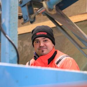 En man med svart mössa står på en stor maskinell såg.