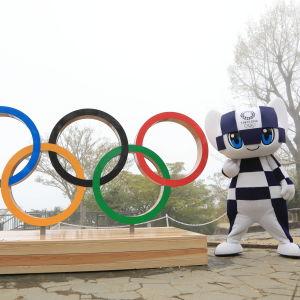 OS-maskoten står bredvid de olympiska ringarna.