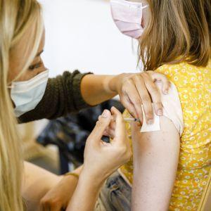 En ung person får coronavaccin.
