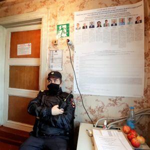 Mustanharmaassa univormussa oleva lippalakkipäinen poliisi vartioi äänestyspaikkaa radiopuhelin kädessään ja maski kasvoillaan. Seinällä hänen yllään näkyy ehdokaslista.