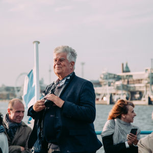 A man standing on the outside deck of a ferry boat. The finnish flag in the background.