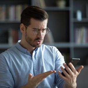 Man med glasögon tittar argt på sin telefon och slår ut med händerna