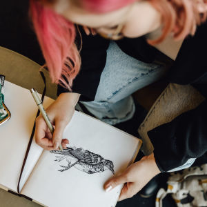 Evelina Blom, en flicka med rödaktigt hår, lutar sig över att ritblock där hon tecknar en fågel.