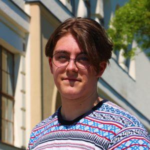 En ung man med kort brunt hår och glasögon.