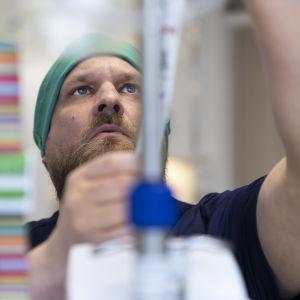 Mikko Tarvonen säätää laitteita sairaalassa.