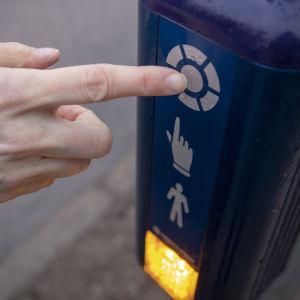 En hand trycker på knappen för trafikljuset vid ett övergångsställe.