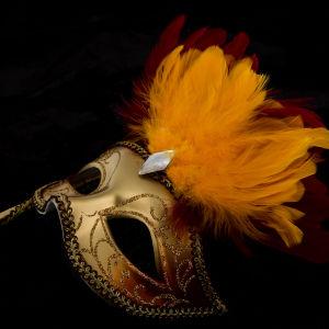 En mask i guld med en orange fjäder.