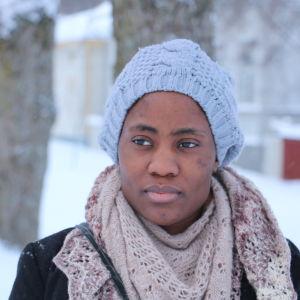 En nigeriansk kvinna med mössa på huvudet och halsduk runt halsen. I bakgrunden syns träd och snö.