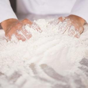Två händer bakar med mjöl på ett bord.