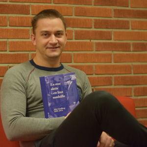 En man sitter på en soffa och håller i en bok.