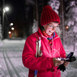 Keski-ikäinen nainen kuuntelee audiosisältöjä Yle Areenasta samalla kun on hiihtolenkillä talvisena iltana.