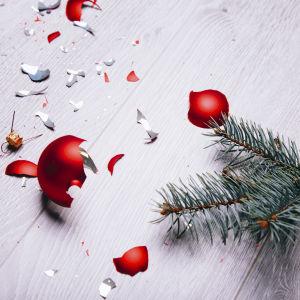 En trasig julgransboll på golvet bredvid en grankvist.