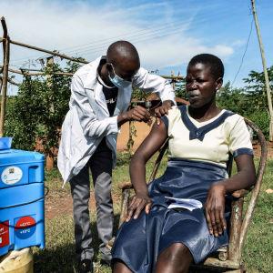 Terveystyöntekijä antaa rokotuksen Keniassa.