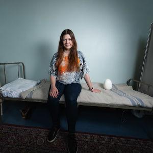 Hanna Bergholm istuu lapinlahden sairalassa Aleksis Kiven vanhalla rautasängyllä vieressään iso muna.
