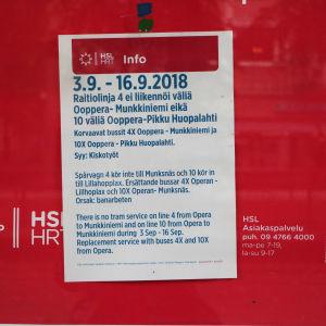 En lapp med information på finska, svenska och engelska på röd bakgrund.