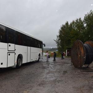 En vit buss står  vid en busshållplats och tar upp passagerare. Skolbarn. Det är ganska mörkt och regnigt.