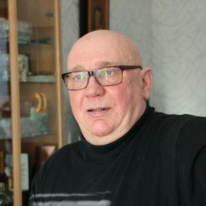 En skallig man med glasögon sitter på en stol.