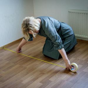 Nainen mittailemassa kontallaan lattialla tyhjässä asunnossa.