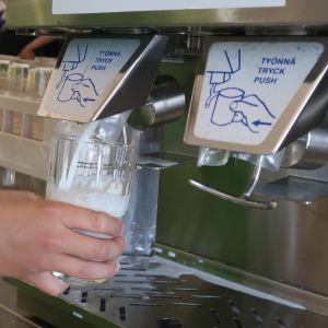 En hand som fyller ett glas med mjölk i en mjölkmaskin