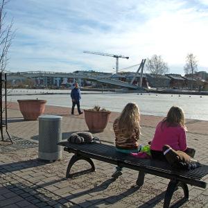 Två flickor som sitter på en parkbänk och tittar ut över Borgå å.