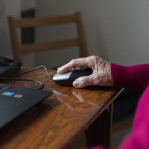En äldre persons hand på en datormus.