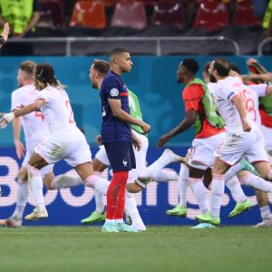 Kylian Mbappé står på planen med tom blick efter förlusten som Schweiz spelare springer omkring i glädjeyra.