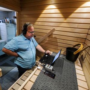 Petteri Löppönen valmistautuu lukemaan radiouutiset etänä kotinsa saunasta Vantaalta.