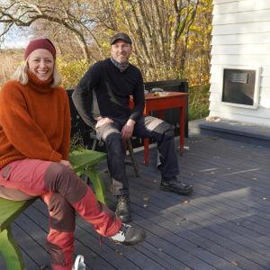 En man och en kvinna i medelåldern som sitter på en bänk och en pall på en svart altan.