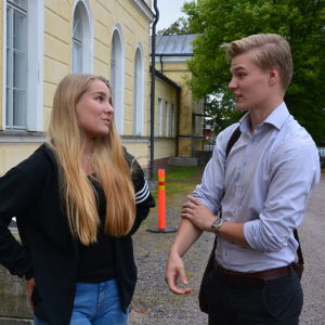 en flicka och en pojke står och pratar med varandra utanför ett gymnasium