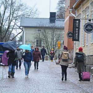 Vädret är regningt och några människor går på en gata i Borgå gamla stad.