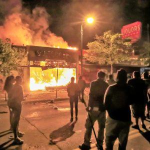 Väkijoukko seisoo kadulla ja katsoo, kun kauppa palaa. On yö.