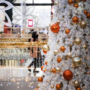 En ung person med munskydd går i ett julpyntat köpcentrum.