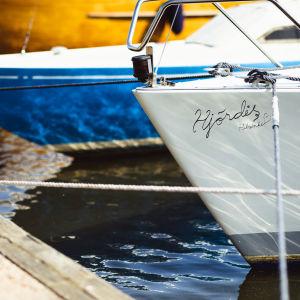 """Två segelbåtar står förtöjda i en brygga. Den ena båten har ingraverat namnet """"Hjördis"""" i fören."""