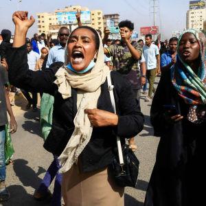 Skanderande kvinna i demonstration.