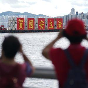 Kaksi hahmoa etualalla katsoo laivaa, joka kuljettaa suurikokoista tekstiä.