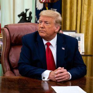 Donald Trump sitter vid ett skrivbord i Vita huset. Han tittar åt sidan.