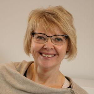 En kvinna med kort blont hår och glasögon skrattar.