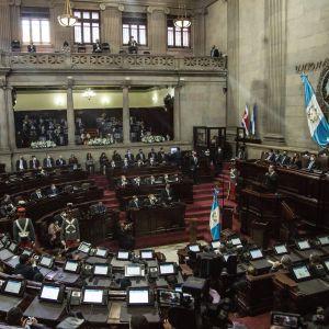 Guatemalan kongressin istuntosali. Presidentti puhuu puhujankorokkeella.