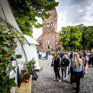 Flera personer köar till en utservering, vid Åbo domkyrka.