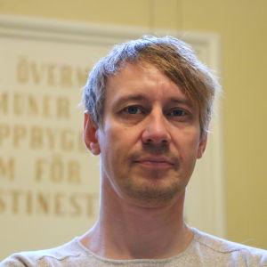 En man i 40-årsåldern i halvprofil. Han har kort ljust hår och skäggstubb.