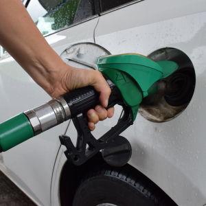 En hand som håller i en bränslepistol vid en bil.