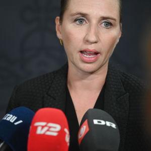 Danmarks statsminister Mette Frederiksen i kostym talar inför pressen. I förgrunden syns tre mikrofoner på hennes bord.