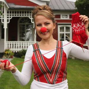 Tv-programmet Strömsös hantverksexpert Lee Esselström står framför Strömsövillan med en röd clownnäsa och håller en halvfärdig röd yllestrumpa. Yllestrumpan är hennes design för Näsdagen 2020.