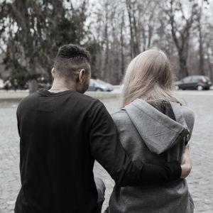 En kille och en tjej sitter och håller om varandra. Vi ser dem bakifrån. De sitter på en parkbänk.