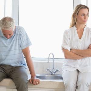 En man sitter med nedböjt huvud och kvinnan bredvid tittar bort.