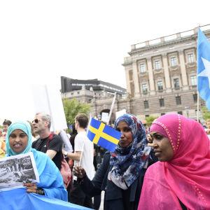 Demonstration utanför Sveriges riksdag. I förgrunden muslimska kvinnor i färgranna slöjor och med Sveriges flagga i handen.