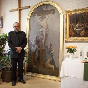 Jouni Heiskanen står brevid altartavlan som han räddade ur den brinnande kyrkan i Joensuu.