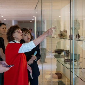 Karin Widnäs visar upp konstverk i ett vitrinskåp i sitt museum Kwum.