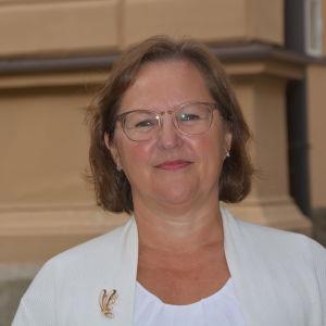 Kvinna framför gul byggnadsfasad.